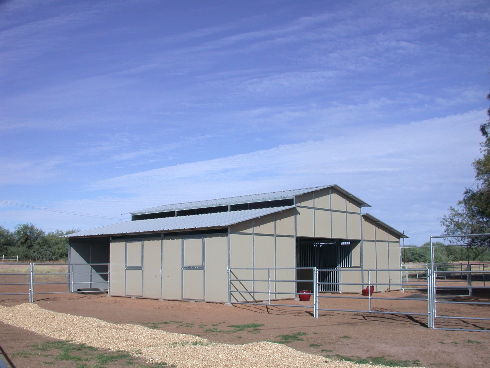 4 stall Raised center aisle breezeway barn, 3:12 pitch roof with one open hay bay shows turnout pipe panels 5' x 4 rails.